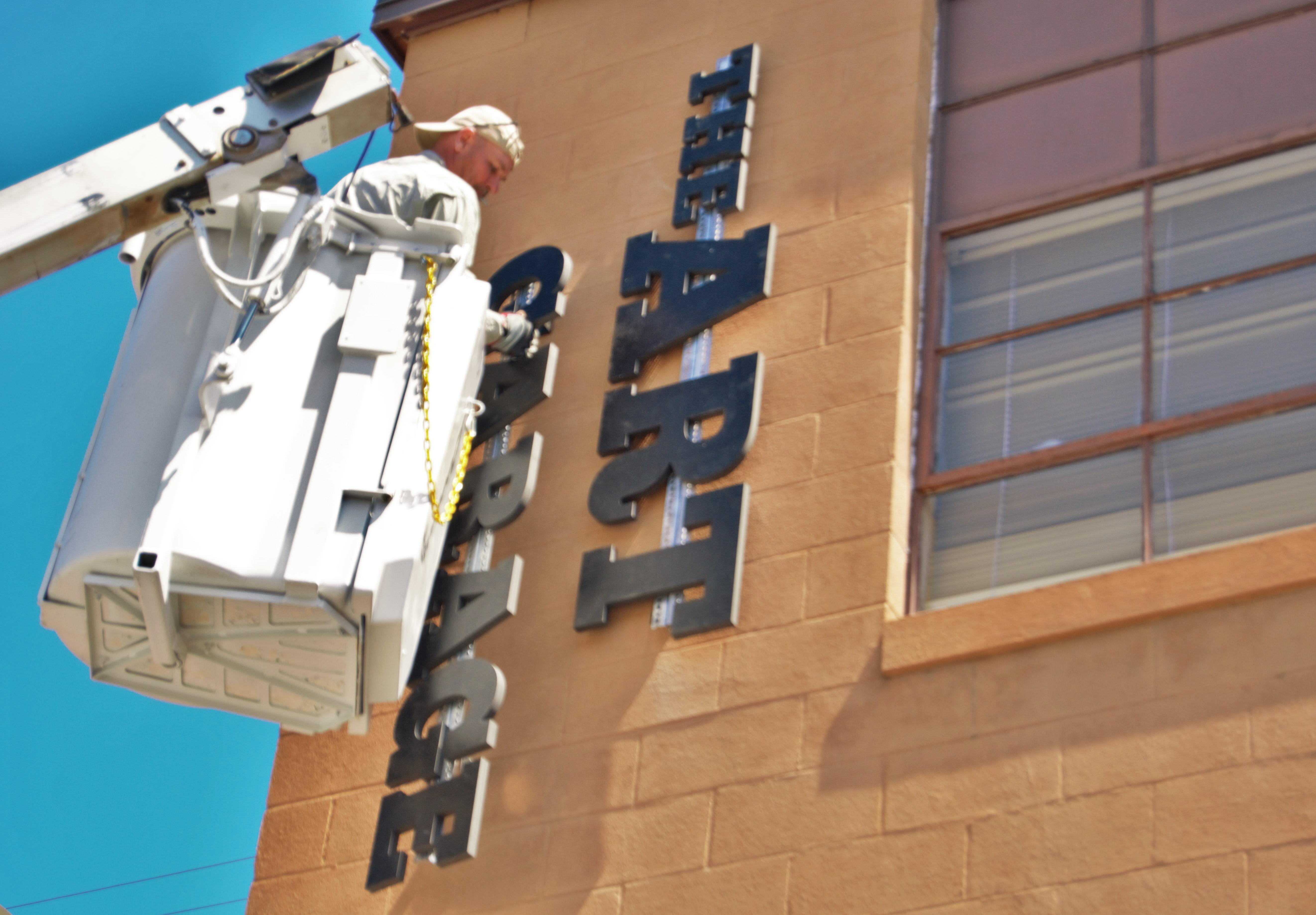 Workers put the finishing touches on the new sign at The Art Garage at Saint Francis